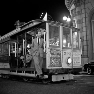 Herb Caen riding a San Francisco Cable Car 1002380